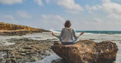Muchacha meditando frente al mar